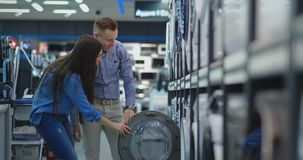 Young married couple man and woman in casual clothes appliances store choose to buy washing machine for home. Open the. Door looking into the drum, compare the stock video