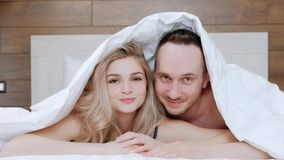 A young married couple, a man and a woman are lying on a bed with white linens. Morning and awakening. stock footage