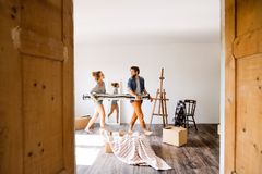 Young couple moving in new house, carrying a carpet. Stock Images