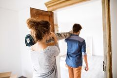 Young couple moving in new house, carrying a carpet. Stock Photo