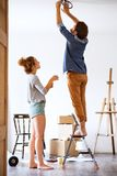 Young couple moving in new house, changing a light bulb. Royalty Free Stock Photo