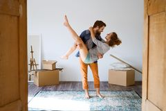 Man carrying woman in his arms, moving in new house. Young married couple moving in a new house, men carrying women in his arms Stock Photos
