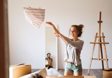 Young couple moving in new house, unpacking things. Royalty Free Stock Image