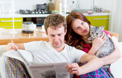 Young married couple in pajamas sitting in the sofa with newspap. Er and cat at home Royalty Free Stock Photo