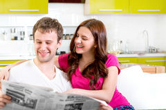 Young married couple in pajamas sitting in the sofa with newspaper and coffee and having fun at home in the morning stock images