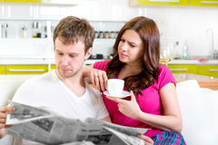 Young married couple in pajamas sitting in the sofa with newspap. Er and coffee and having fun at home in the morning Royalty Free Stock Photo