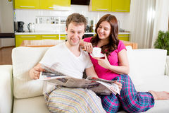 Young married couple in pajamas sitting in the sofa with newspap. Er and coffee and having fun at home in the morning Stock Image