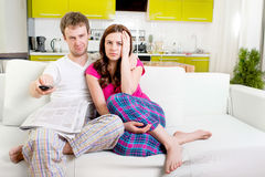 Young married couple in pajamas sitting in the sofa with newspap Stock Photo