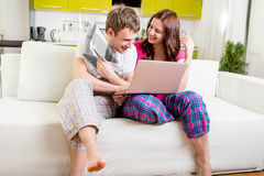 Young married couple in pajamas sitting in the sofa reading news Stock Photos