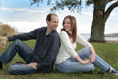 Young Married Couple At The Park. A young married couple having fun in the grass under the trees at a park Royalty Free Stock Photography