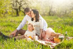 Young married couple on a picnic in the blooming garden or park. Warmly, love, spring and summer mood royalty free stock photo