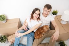 A young married couple with a red cat, a man and a woman, are sitting on the floor in a bright room against the stock image