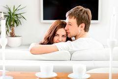 Young married couple sitting on the couch and watching tv at hom Stock Image