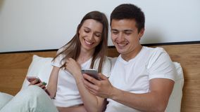 Young married couple sitting on sofa and watching video on the smartphone. Attractive young married couple is sitting on sofa in living room and laughs watching stock video