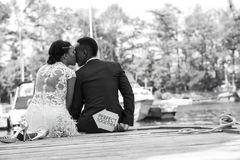 Romantic couple sitting at a wooden dock and express their love royalty free stock photography