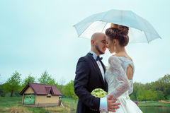 Young married couple smiling on each others under the umbrella Stock Image