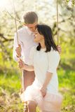 Young married couple, on a swing in a flowered garden or park. Warmly, love, spring and summer mood.  royalty free stock photo