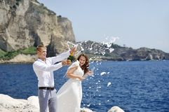 Young married couple uncorking champagne by the sea after their wedding Stock Images