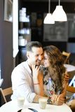 Young married happy couple sitting at cafe and hugging. royalty free stock photography