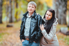 Young married pregnant couple walking in the autumn park. Man and his pregnant wife walks in the autumn Park Stock Photo
