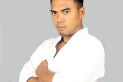 Young martial artist. Asian young posing in white kimono on a gray background Royalty Free Stock Images