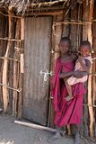 Young Masaai Portrait. A young Masaai girl carrying her little sister and poses to the camera in front of her grandmother's hut. Taken at: Boma na Mungai Royalty Free Stock Photo