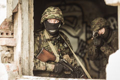 Young masked snipers. Shooting with a pistol Stock Photography