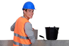 Young mason happily working away Stock Image