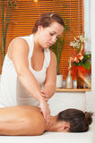 Young massage therapist giving a massage Royalty Free Stock Photography