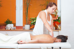Young massage therapist giving massage in massage salon Royalty Free Stock Image