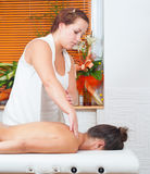 Young massage therapist giving a massage in massage salon Stock Image