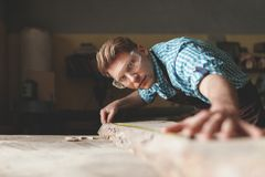 Young master with glasses in carpentry. Young master with glasses measuring in carpentry Royalty Free Stock Images