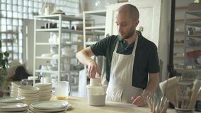 Young master immerses mug in liquid at desk pottery workshop. stock video