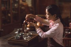 Young master pouring tea from a teapot Royalty Free Stock Image