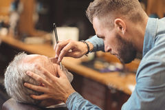 Young master shaving beard of the client in the barbershop royalty free stock photography