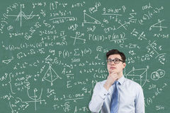 Young math genius portrait. Young math genius solving a difficult equation while standing near green chalkboard with formulas. Concept of engineering Stock Photos