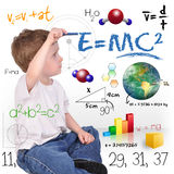 Young Math Science Boy Genius Writing. A young boy child is writing out math and science equations and formulas. He is sitting on the floor on a white background Royalty Free Stock Images