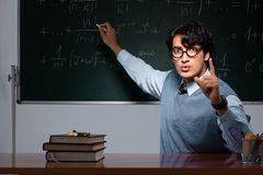 The young math teacher in front of chalkboard. Young math teacher in front of chalkboard royalty free stock photography