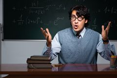 The young math teacher in front of chalkboard. Young math teacher in front of chalkboard royalty free stock photos