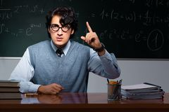 The young math teacher in front of chalkboard. Young math teacher in front of chalkboard stock photos