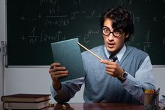 The young math teacher in front of chalkboard. Young math teacher in front of chalkboard royalty free stock images