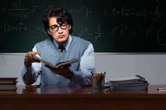 The young math teacher in front of chalkboard. Young math teacher in front of chalkboard stock photography