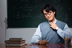 The young math teacher in front of chalkboard. Young math teacher in front of chalkboard stock images