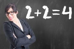Young math teacher writing numbers on the chalkboard. As concept of education royalty free stock photography