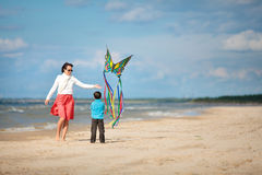 Young mather and her son playing with kite. On the beach Royalty Free Stock Image