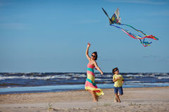 Young mather and her son playing with kite. On the beach Royalty Free Stock Photography