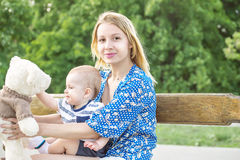 Young mather with a little son sitting on her knees with a toy on a bench in a park. Portrait of pretty mather with baby outdoor in summer park Royalty Free Stock Photos