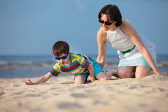 Young mather and son playing on the beach.  Royalty Free Stock Photo