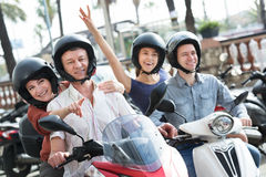 Young and mature couples driving petrol scooters. Young and mature happy couples driving a petrol scooters outside and smiling. Focus on mature men and mature royalty free stock photo
