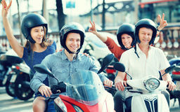 Young and mature couples driving petrol scooters. Outside and smiling. Focus on young man stock photo